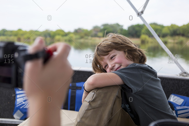 A five year old boy smiling at the camera on a river boat on the Zambezi River.