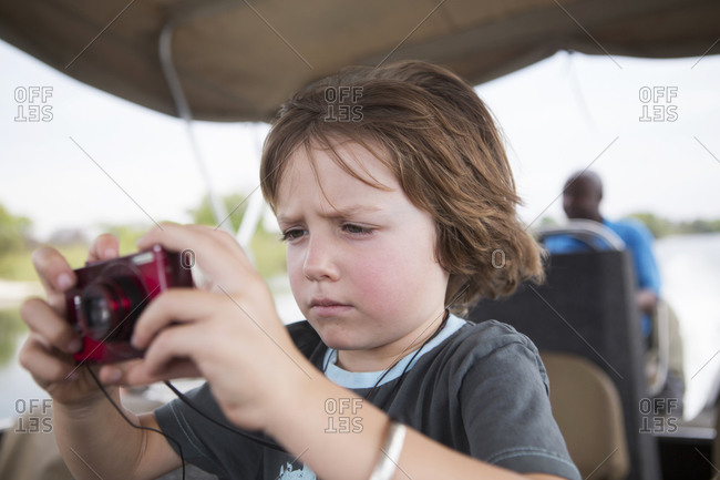 A five year old boy using his red camera, taking pictures on a river boat on the Zambezi River.