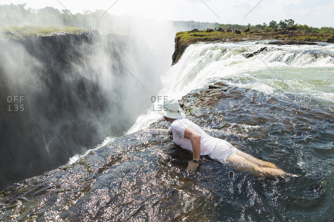 Man in the water on the edge of Victoria Falls, looking over the waterfall edge.