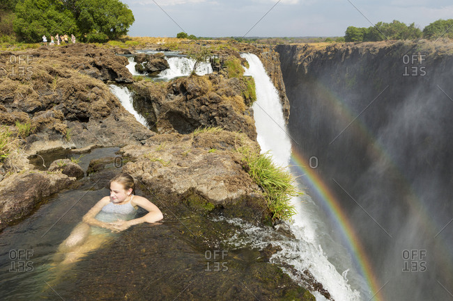 Young Teenage girl in the water on the cliff top overlooking Victoria Falls, view from above.
