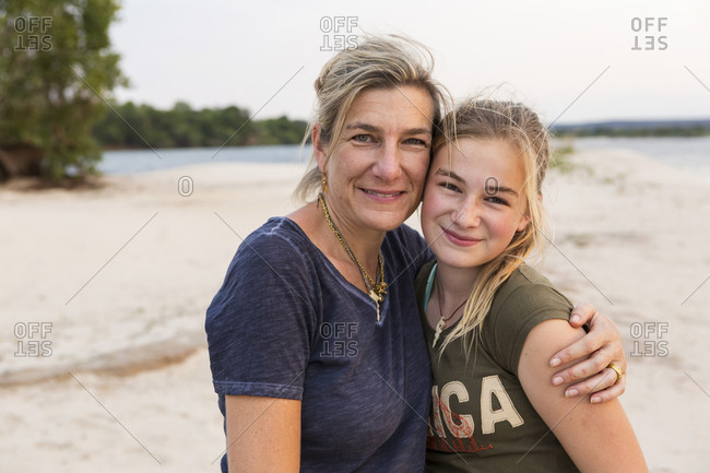 Mature woman and a young Teenage girl, mother and her daughter on the banks of a wide river.