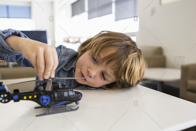 A five year old boy playing with a toy tractor on a table in an airport departure lounge.