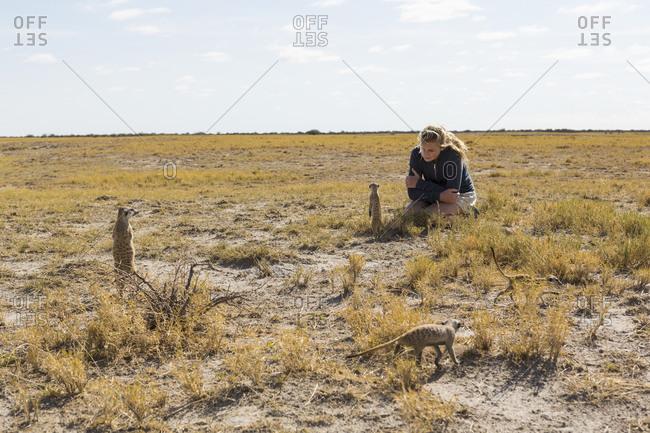 Twelve year old girl looking at Meerkats, Kalahari Desert