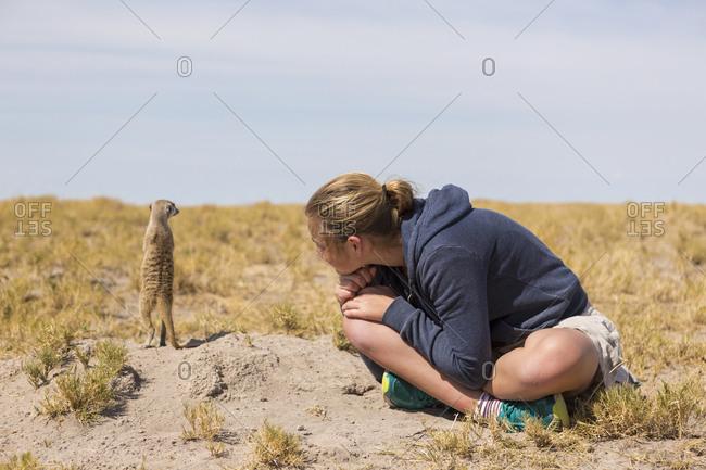 Twelve year old girl sitting watching meerkats emerge from their burrows, in the Kalahari desert.
