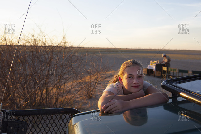 Twelve year old girl leaning on the roof of a jeep in the Kalahari Desert at sunset.