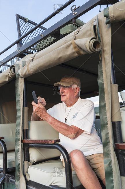 senior man taking picture with smart phone, Kalahari Desert, Makgadikgadi Salt Pans, Botswana