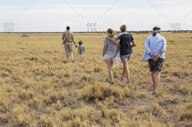 family looking at Meerkats (mongoose), Kalahari Desert, Makgadikgadi Salt Pans, Botswana