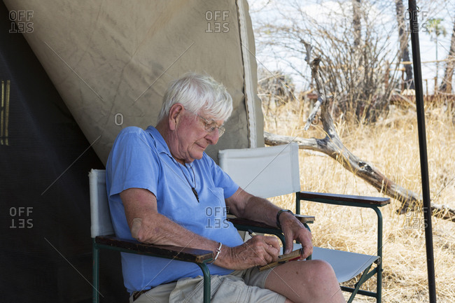 Senior man writing a journal seated outside a tent in a wildlife safari camp.