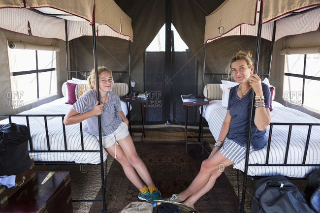 Accommodation at a wildlife reserve camp, a mother and daughter seated on beds in a tent.