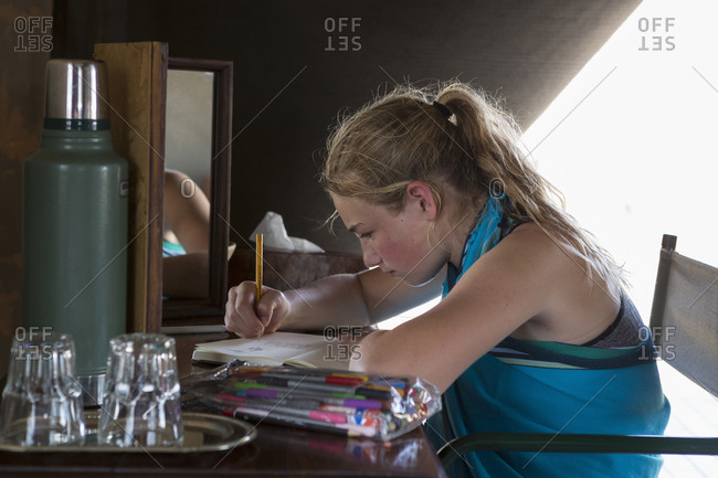 A twelve year old girl seated at a desk in a tent at a wildlife reserve camp, drawing.