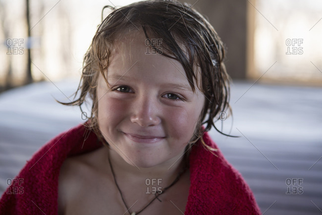 A five year old boy with wet hair and a red towel, smiling.