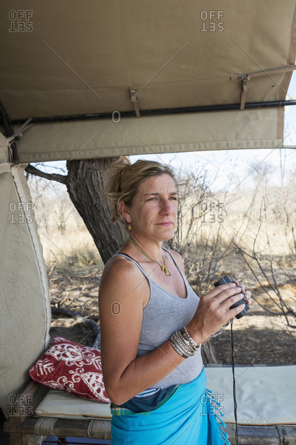 Mature woman by a tent in a wildlife reserve camp holding binoculars