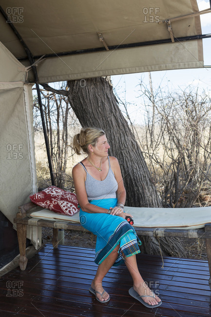 Mature woman seated under canvas, by a tent in a wildlife reserve camp.