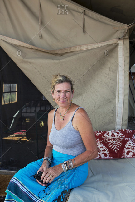 A woman seated on a bed in a tent at a wildlife reserve camp.