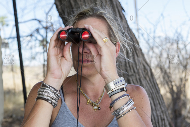 A woman using binoculars in a wildlife reserve camp.