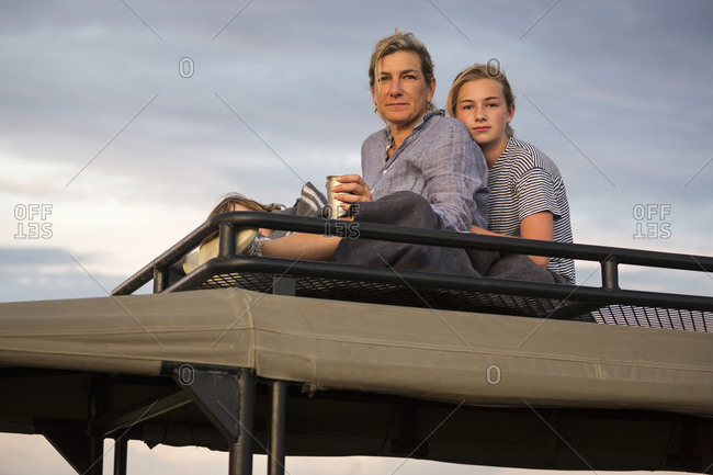 Mother and Teenage daughter on top of safari vehicle looking into the distance.
