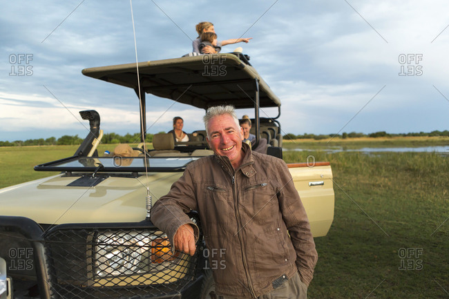 A smiling safari guide and family of tourists in a safari vehicle.
