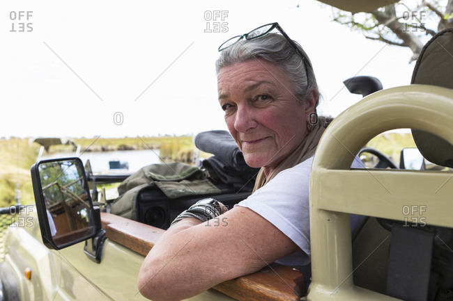 A senior woman in the front seat of a safari keep in a wildlife reserve.