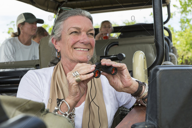 A family in a safari jeep in a wildlife reserve, a senior woman with binoculars.