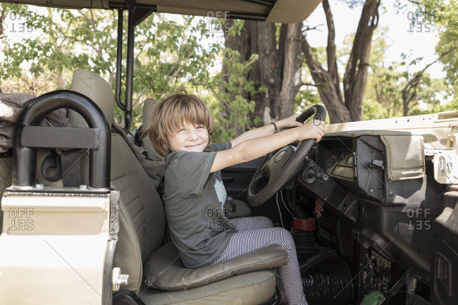 A five year old boy seated in the driving seat of a safari jeep pretending to drive.