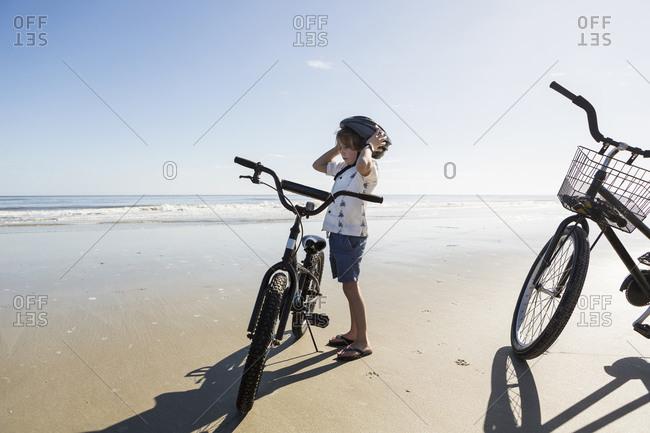 A boy putting on a cycle helmet on the beach, St. Simon's Island, Georgia