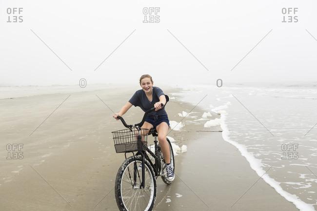 Teenage girl riding a bike on sand at the beach, St. Simon's Island Georgia