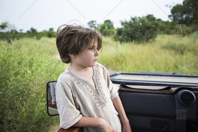 Six year old boy standing looking around the landscape in a safari jeep.
