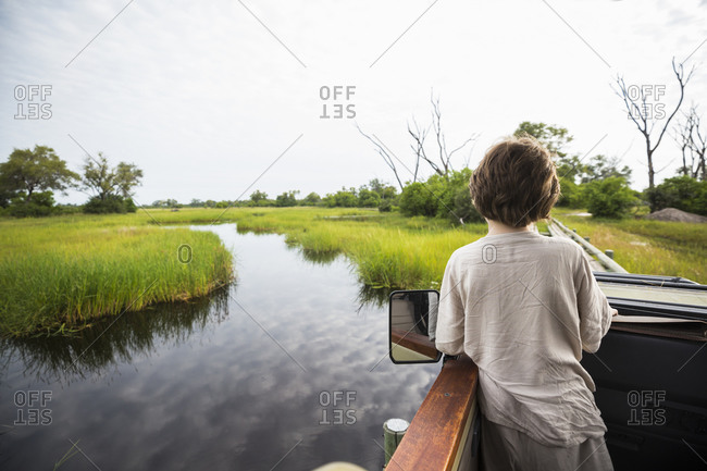 A six year old boy in a jeep on a bridge overlooking marshes and water.