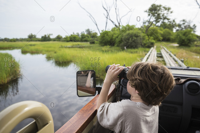A six year old boy using binoculars looking over water from a safari vehicle