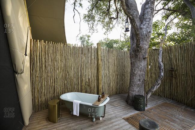 A outdoor bath tub in a tented safari camp