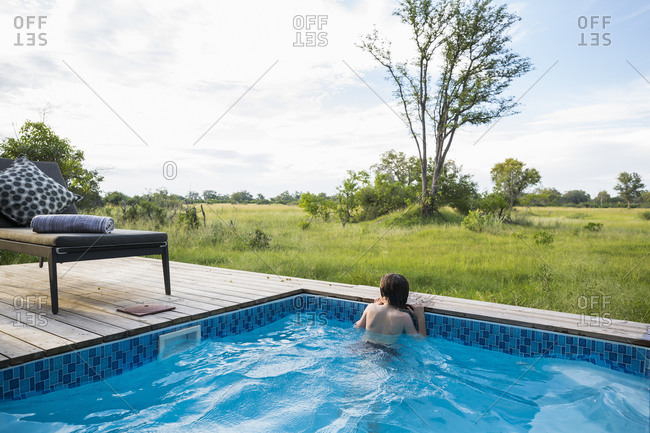 A boy in a swimming pool looking out at the landscape around a safari camp
