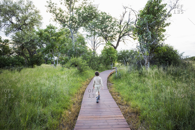 A six year old boy walking on wooden path at a tented safari camp