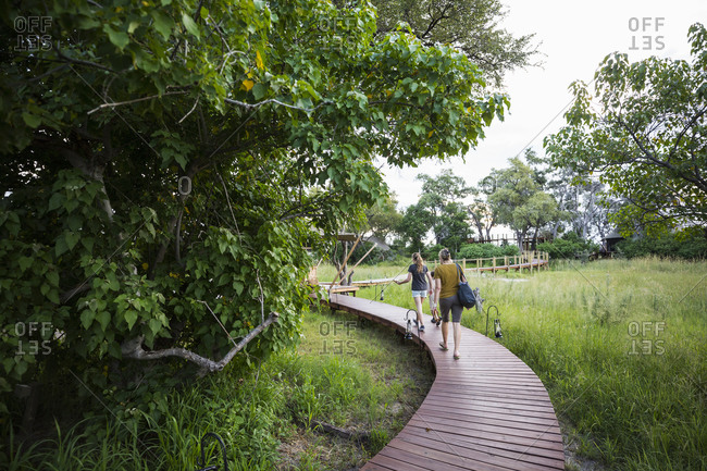 Two people, mother and teenage daughter walking on wooden path at a tented safari camp