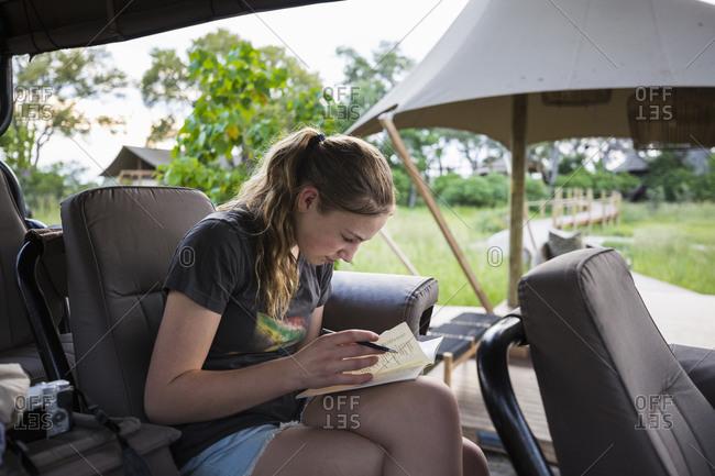 A Teenage girl writing in her journal on safari