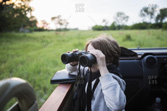 A six year old boy using binoculars seated in a safari jeep.
