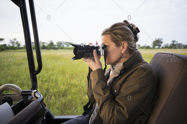 Adult woman using camera seated in a safari jeep in open landscape