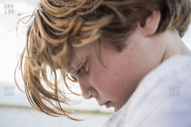 Close up profile of a Six year old boy looking down, head and shoulders