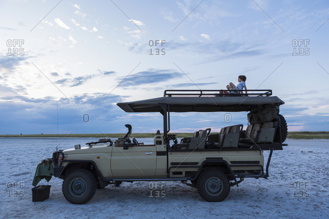 A six year old boy and his Teenage sister sitting on top of a safari vehicle at dusk