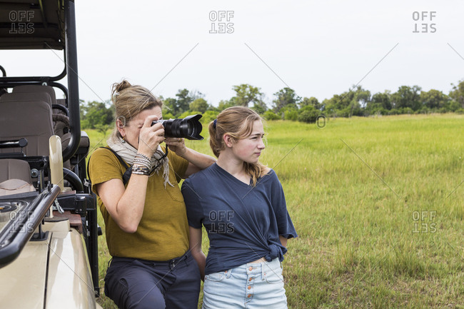 A mother and daughter, a woman and Teenage girl taking photographs on safari
