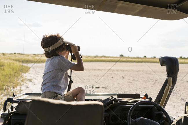 A six year old boy looking through binoculars across a salt pan