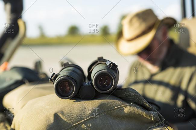 Binoculars on the dash of a safari jeep, a safari guide in the background.
