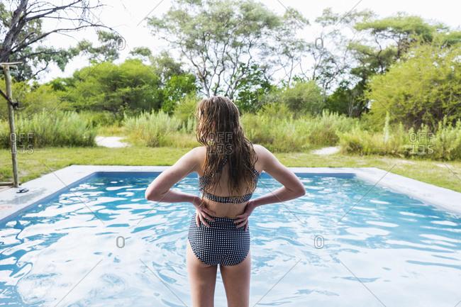 rear view of Teenage girl looking at pool, Maun, Botswana