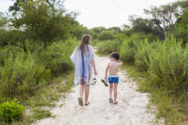 Teenage girl and a young boy, sister and her brother walking on a path in a safari bush camp