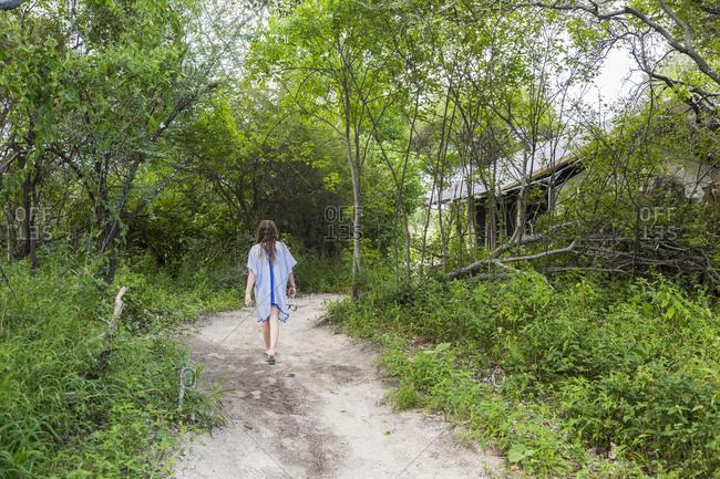 Teenage girl walking on dirt path to tented camp, Maun, Botswana