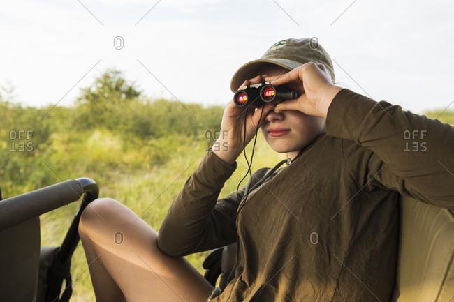 Teenage girl with binoculars on safari vehicle, Botswana