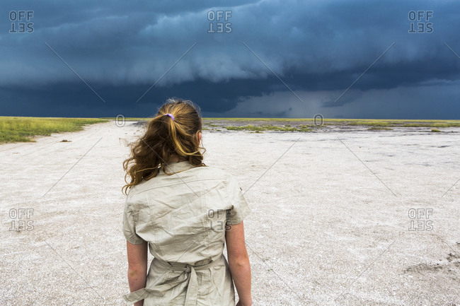 rear view of Teenage girl looking at dramatic sky, Nxai Pan, Botswana