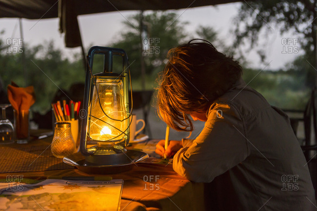 Six year old boy writing a journal by lantern light in a tented camp.