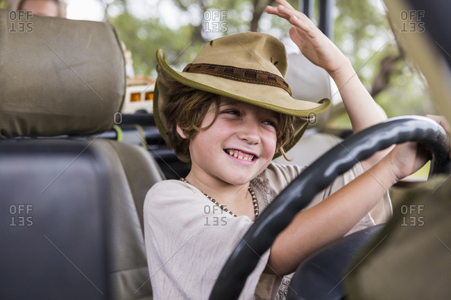 Smiling Six year old boy in the driving seat of a safari vehicle.
