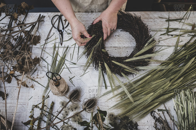 Woman making a winter wreath, adding dried grasses and seedheads and twigs with brown leaves.
