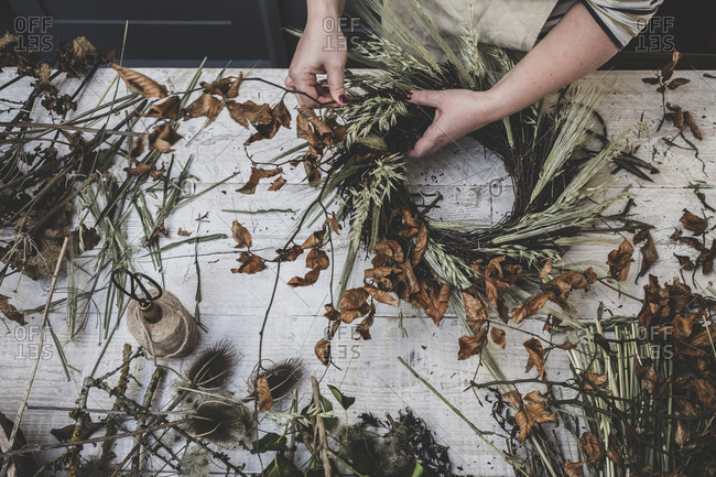 Woman making a small winter wreath of dried plants, brown leaves and twigs, and seedheads.